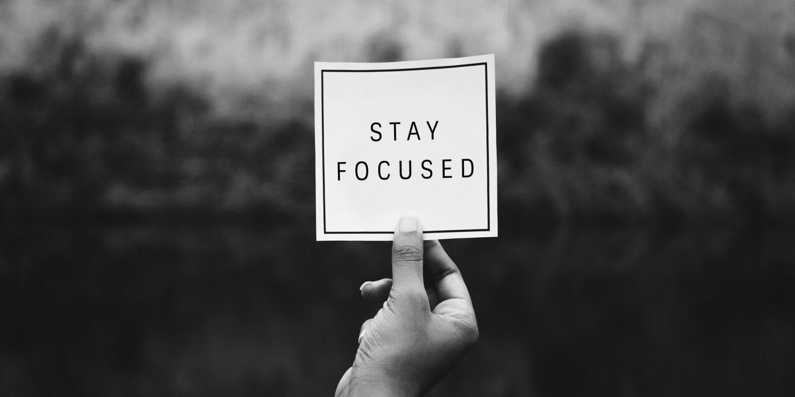 Ръка държи бележка с надпис Stay Focused