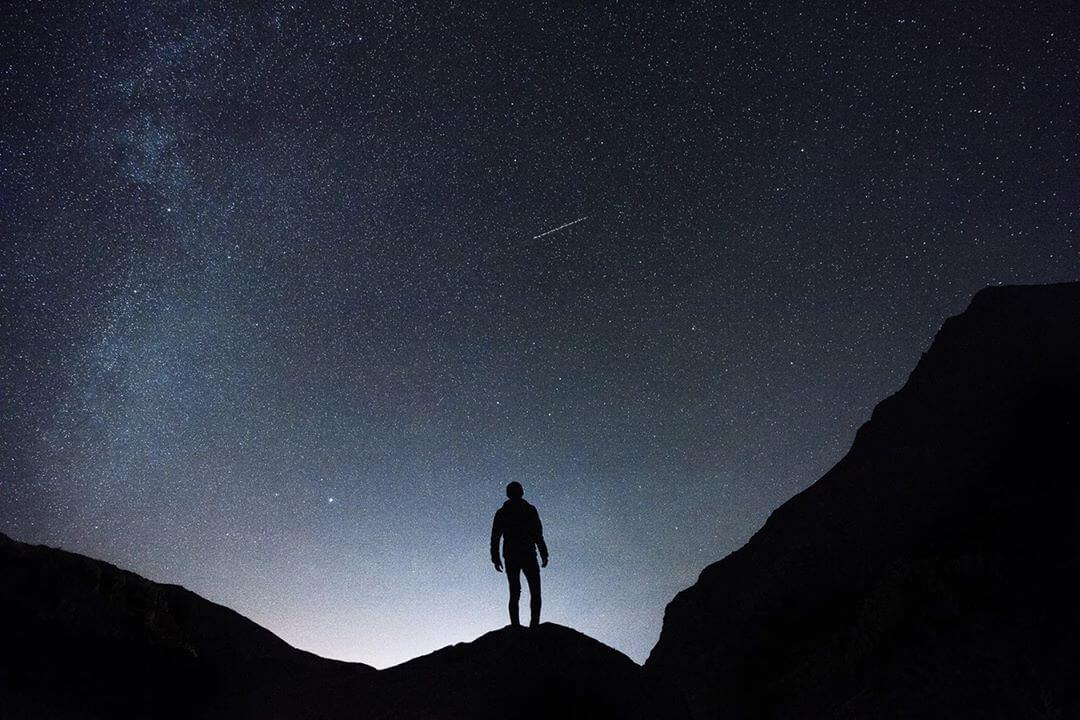 Снимка на човек в планината под нощно небе със звезди